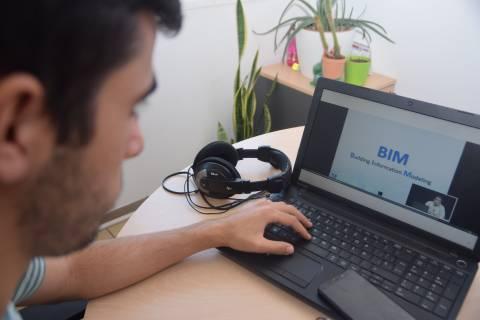 Un joven observando una conferencia sobre metodología BIM grabada en la UPCT.