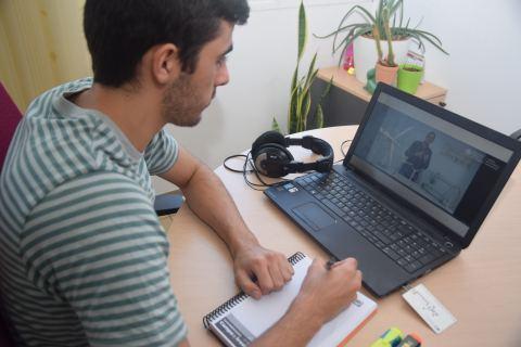 Un joven viendo en un portátil un vídeo docente de la UPCT.