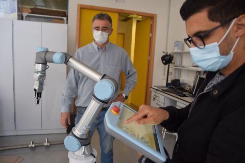 El doctorando Maroaune Salhaoui, junto a su tutor en la UPCT, Antonio Guerrero, probando un robot colaborativo para la Industria 4.0.