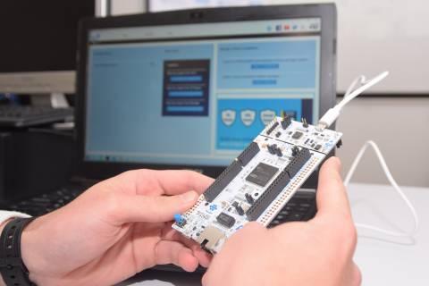 Un alumno observando la tarjeta electrónica y el software con los que realizará la programación en C.