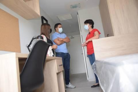 La directora de la residencia muestra la habitación piloto a dos estudiantes.
