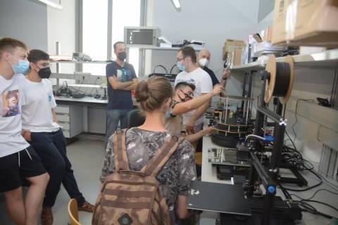 Estudiantes rumanos midiendo el robot asistencial para el que diseñan e imprimirán su carcasa exterior.