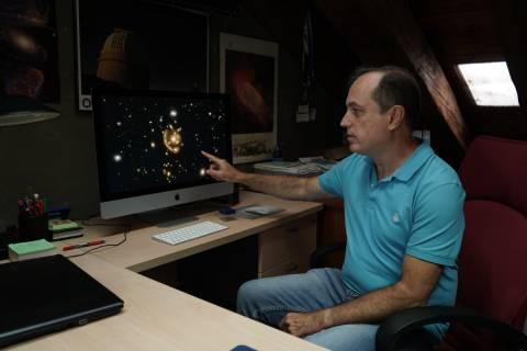 Anastasio Díaz, en su despacho de la UPCT, mostrando las cuatro imágenes de la galaxia que aparentan la forman de un anillo.